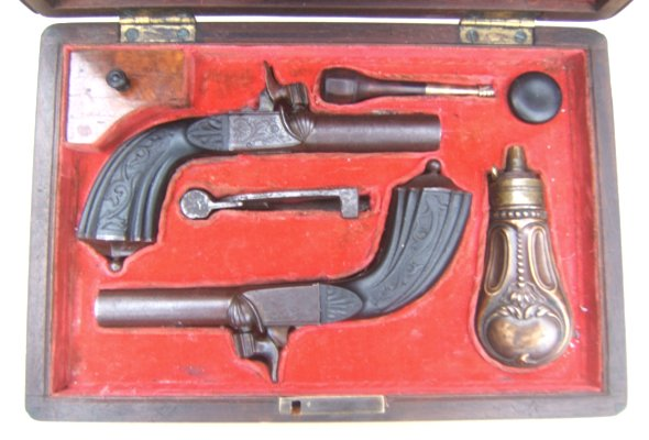 A FINE CASED PAIR OF EBONY STOCK FRENCH PERCUSSION MUFF PISTOLS, dtd. 1840 view 1
